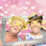 2 guests in the photo booth with a silver picture frame and enjoying our Bournemouth photo booth hire service.
