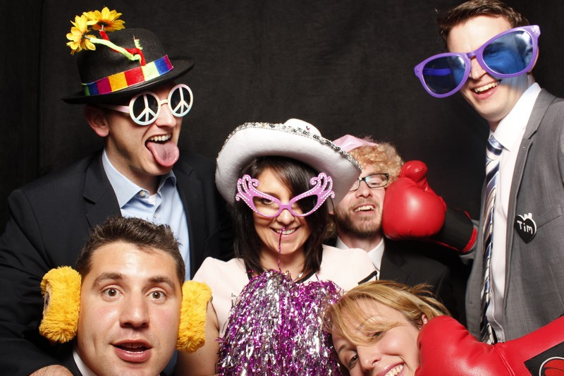Six friends in the photo booth with loads of props